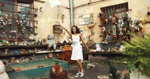 Lächelndes wenig 10 Jahre Mädchen tanzt Ballett mit transparentem Regenschirm im ruinierten Garten mit Spielwaren 4K stock video