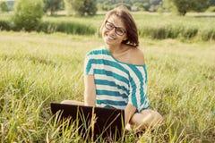 Lächelndes womanl, das auf dem Gras am hellen Sommertag sitzt und an dem Computer arbeitet Unter Verwendung des Laptops draußen,  Stockfoto