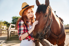 Lächelndes zartes Cowgirl der jungen Frau mit ihrem Pferd auf Ranch lizenzfreies stockfoto