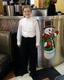 Lächelndes zehnjähriges Mädchen, das nahe bei einem Bild eines Schneemannes steht Stockfotografie