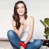 Lächelndes zufälliges Brunettemädchen, das rote Blume hält Stockfotos