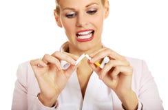 LächelnGeschäftsfrau, die eine Zigarette bricht stockfotos