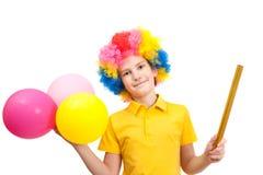 Lächelnjunge in der Clownperücke mit Ballonen Stockbild