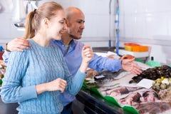 Lächelnmann und kaufende Fische des jungen Mädchens Lizenzfreie Stockfotografie
