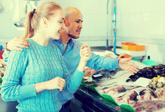 Lächelnmann und kaufende Fische des jungen Mädchens Stockfotos