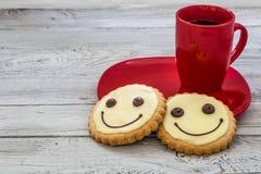 Lächelnplätzchen auf einer roten Platte mit Tasse Kaffee, hölzerner Hintergrund, Lebensmittel Lizenzfreies Stockfoto