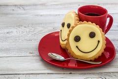 Lächelnplätzchen auf einer roten Platte mit Tasse Kaffee, hölzerner Hintergrund, Lebensmittel Stockbilder