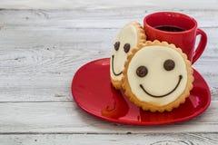 Lächelnplätzchen auf einer roten Platte mit Tasse Kaffee, hölzerner Hintergrund, Lebensmittel Lizenzfreie Stockfotografie