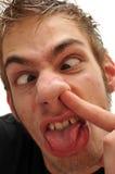 Lächerlicher Mann, der seine Wekzeugspritze mit gekreuzten Augen auswählt Stockbilder