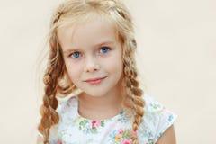 Lächerliches blondes Mädchen des Porträts mit Zöpfen und blauen runden Augen Lizenzfreie Stockbilder