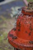 Läcka brandposten som besprutar vatten Arkivfoto