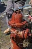 Läcka brandposten som besprutar vatten som stänger sig med skiftnyckeln Royaltyfria Foton