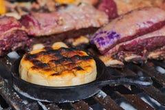 Läcker argentinsk Provolonegarnost Provoleta som lagas mat i en gjutjärnkastrull över gallret av en grillfest royaltyfri foto