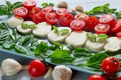 Läcker caprese sallad på den gråa plattan med organiska ingredienser: skivad mozzarellaost, körsbärsröda tomater, nya basilikasid royaltyfria foton