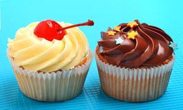 Läcker choklad, krämiga muffin på blå bakgrund Arkivbild