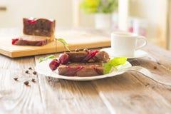 Läcker chokladkaka på plattan och skärbräda på brun lantlig tabellbakgrund Royaltyfri Bild