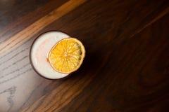 Läcker coctail på naturlig träyttersida Tjäna som i härligt exponeringsglas med den torkat apelsinen och skum royaltyfri fotografi