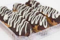 Läcker eclair som tre täckas med chokladisläggning Arkivbild