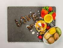 Läcker efterrätt på en svart stenplatta med pudding och macaro Fotografering för Bildbyråer