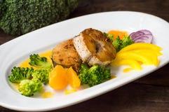 Läcker filéfisk som grillas i stekpannan Postat med tangerinsås, peppar och skivor av kokt broccolialdente trä Arkivfoton