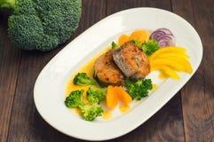 Läcker filéfisk som grillas i stekpannan Postat med tangerinsås, peppar och skivor av kokt broccolialdente trä Arkivbilder