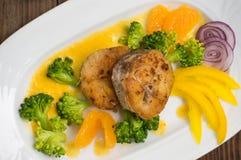Läcker filéfisk som grillas i stekpannan Postat med tangerinsås, peppar och skivor av kokt broccolialdente trä Fotografering för Bildbyråer