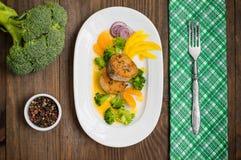 Läcker filéfisk som grillas i stekpannan Postat med tangerinsås, peppar och skivor av kokt broccolialdente trä Royaltyfri Foto