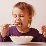 Läcker frukost som lilla flickan önskar att äta Barn` s f Arkivfoto
