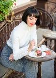 Läcker gourmet- kaka Attraktiv brunett för kvinna att äta gourmet- bakgrund för kakakaféterrass Gastronomical njutning arkivbild