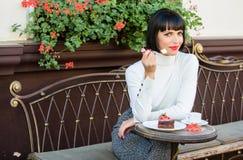Läcker gourmet- kaka Skämma sig bort Flickan kopplar av kafét med kakaefterrätten Attraktiv elegant brunett för kvinna att äta fotografering för bildbyråer