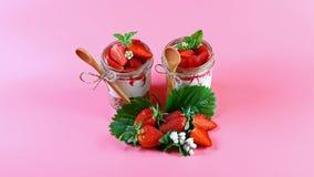 Läcker granola med frukter, jordgubbeyoghurt med nya bär, träsked för havremjölkakor kopiera avstånd arkivbilder