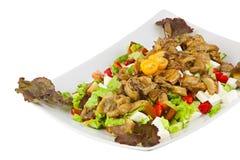 Läcker grekisk sallad på plattan på vit bakgrund arkivfoton