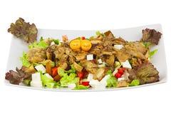 Läcker grekisk sallad på plattan på vit bakgrund royaltyfri foto