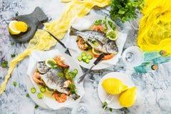 Läcker grillad dorado- eller havsbraxenfisk med citronen och nya räkor, ny persilja och spenat på det vita uppläggningsfatet royaltyfri bild