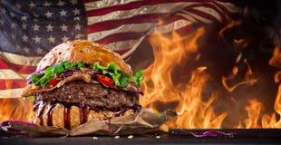 Läcker hamburgare med brandflammor Arkivfoto