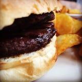 Läcker hamburgare med frasiga kilar på sidan Arkivfoton