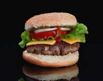 Läcker hamburgare med nötkött med ost, tomater, lökar, gurkor och tomater och ketchup på en svart bakgrund och på en bla arkivbilder