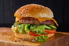 Läcker hamburgare med nötkött, tomater, sallad och sås ombord på träbakgrund Arkivfoto