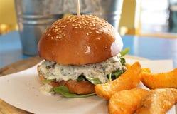 Läcker hamburgare med småfiskar för vit sås och potatis Royaltyfria Bilder
