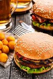 Läcker hamburgare med stekt potatisbollar och öl Arkivfoto