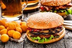 Läcker hamburgare med stekt potatisbollar och öl Arkivbilder