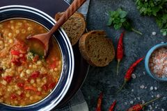 Läcker hemlagad soppa från den organiskt röda linsen, grönsaker, basilika, vitlök och stycke av svart bröd på den mörka stentabel arkivbild