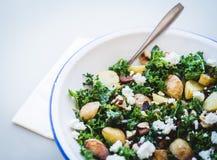 Läcker hemlagad stekpotatis, grönkål och sallad för fetaost med muttrar royaltyfri fotografi