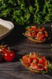 Läcker italiensk antipastibruschetta med högg av tomat-, köttpate-, sås-, gräddost- och salladsidor St arkivbild