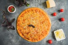 Läcker italiensk pizza med bacon-, ost-, tomat- och basilikasidor på mörk bakgrund Lekmanna- lägenhet, bästa sikt royaltyfria bilder