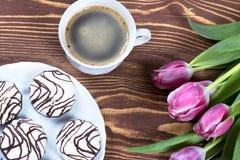 Läcker kaka med coffe och tulpan på tabellen Arkivfoto