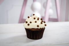 Läcker liten kaka med vit isläggning och bruna sötsaker Royaltyfri Fotografi