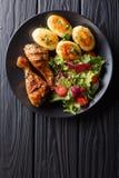 Läcker mat: grillade fega trumpinnar med nya potatisar och Arkivfoto