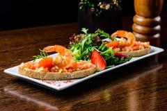 läcker maträttskaldjur Bröd med tomater och räkor och basi arkivbilder