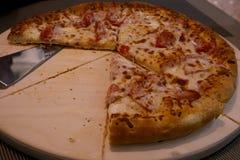 Läcker matställe, saftig pizza med ost, tomater och kött på ett trämagasin arkivbilder